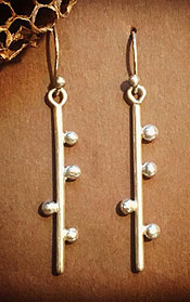 Earrings with balls along a post, by Cara Wolff