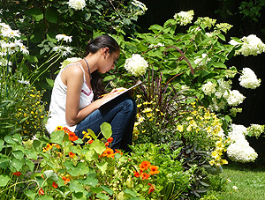 A student writing in the gardens at The Poetry Studio