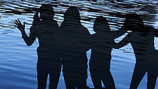 Children's silhouettes on river